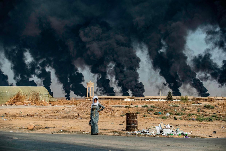 Terwijl Turkse oorlogsvliegtuigen bommen droppen, staat een vrouw te wachten langs de weg in Tal Tamr, vlak bij de Turkse grans.