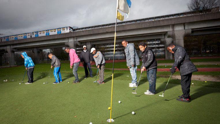 Chris Ogar (vierde van links) met zeven leerlingen op het golfterrein bij Kruitberg in Zuidoost. © Marc Driessen Beeld