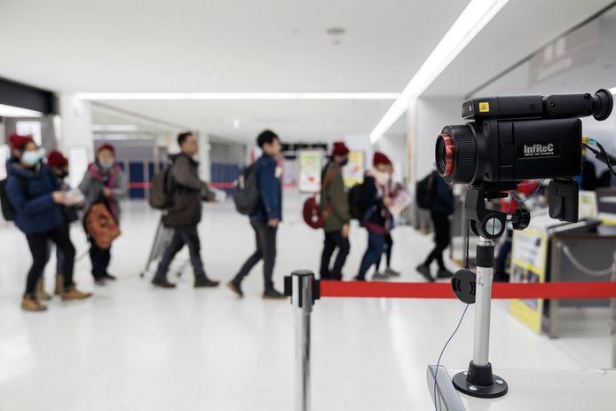 Passagiers van een vlucht uit China lopen op de luchthaven Narita bij Tokio langs een scanner die lichaamstemperatuur  meet.  Een groeiend aantal landen controleert met dergelijke apparatuur mensen op een mogelijke besmetting met het mysterieuze corona-virus uit China dat inmiddels aan twee mensen het leven heeft gekost. (Foto Tomohiro Ohsumi/Getty Images)
