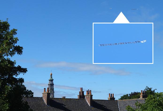 Het vliegtuigje boven het centrum van Middelburg. Inzet: vlag met de tekst 'terreur-revolutie'.