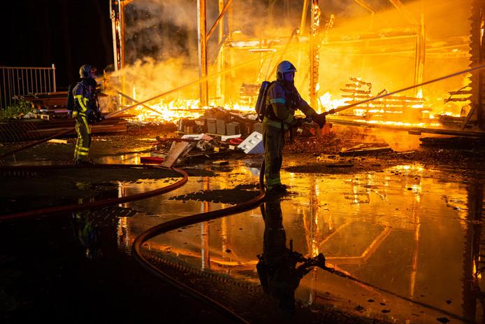 Een brandweerman bestrijdt het vuur in een loods in Oldebroek.