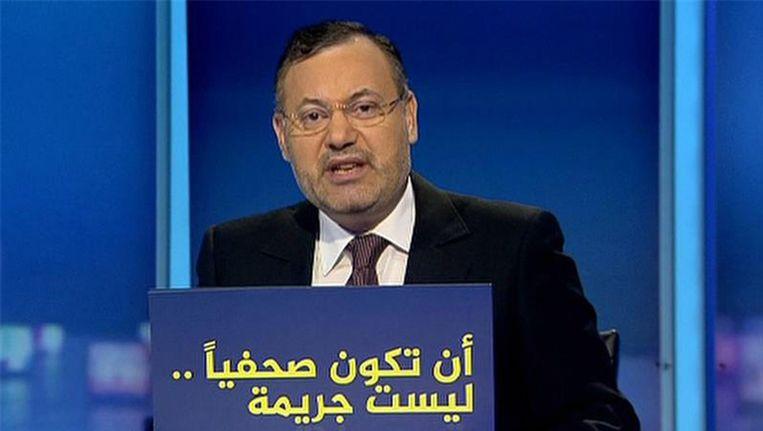 Mansour voor een bord met de tekst: journalistiek is niet een misdaad. Beeld afp