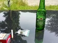 Bestuurder drinkt een biertje tijdens het rijden