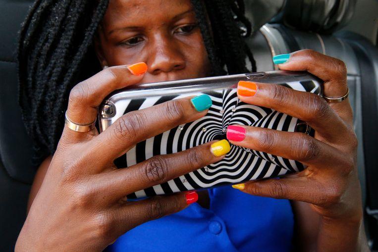 Een vrouw in Oeganda zit op haar mobiele telefoon. Beeld Getty