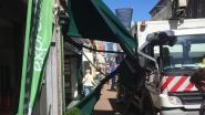 Oeps: vrachtwagen blijft haperen aan luifel van winkel: brandweer moet metaal uit portier knippen