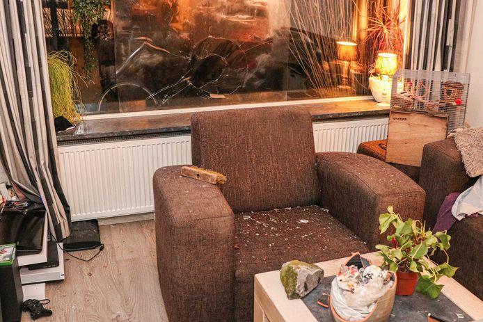De ingegooide ruit van een woning aan de Rijnstraat. Op tafel de kei waarmee de ruit is ingegooid.