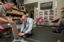 Thijs van Oorschot helpt een klant in zijn schoenenzaak aan de Steenweg.