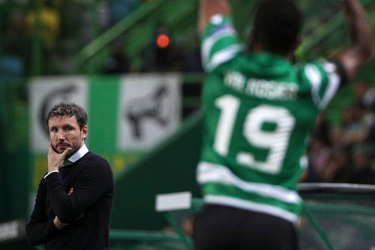 Een getergde Mark van Bommel kijkt toe terwijl zijn ploeg over de knie wordt gelegd door Sporting Portugal.  Beeld AFP