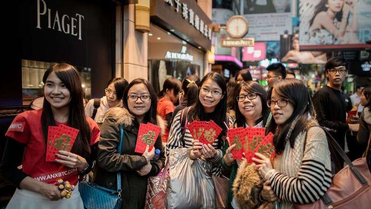Promotiestunt in Hong Kong: winkelend publiek krijgt bitcoin-coupons ter gelegenheid van het Chinese nieuwjaar. Beeld afp