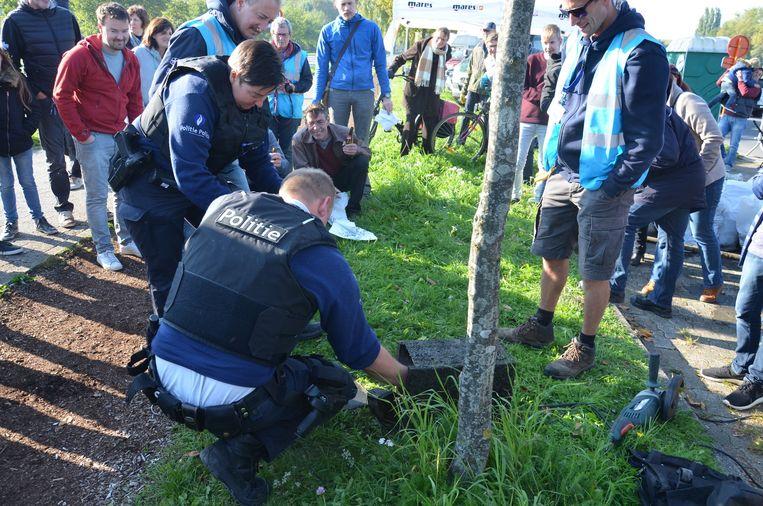 Onder grote belangstelling haalde de politie een brandkast leeg die uit het water was gevist. Er zat enkel wat kleingeld in.