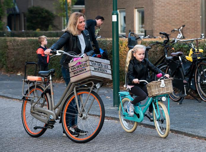 Een kind op de fiets wordt begeleid naar basisschool De Schakel. De Fietsersbond en de school hopen dat andere ouders dat ook vaker doen.