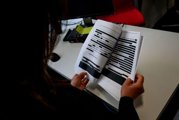 Een journalist probeert tussen de zwartgemaakte regels door het rapport van Mueller te lezen.  Beeld Foto AFP