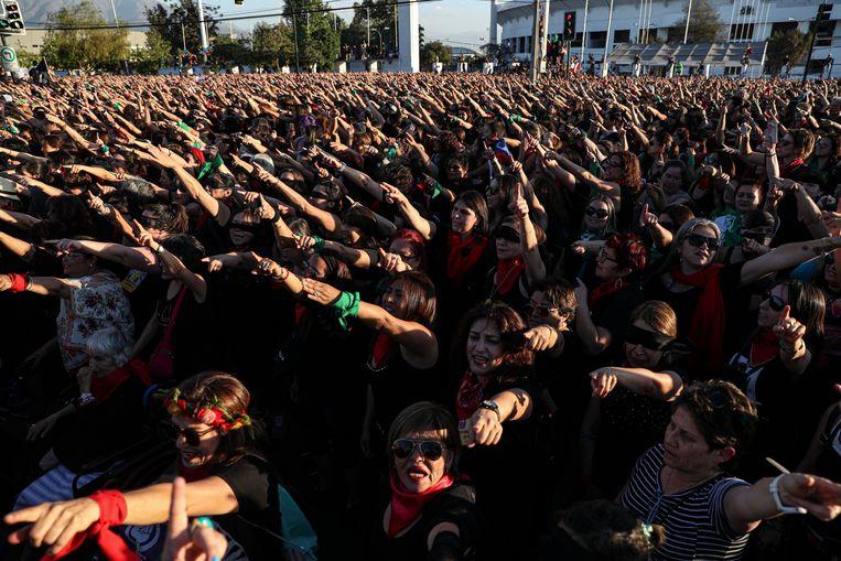 Vrouwen zingen het protestlied 'Un violador en tu camino' tijdens een flashmob in de Chileense hoofdstad Santiago. De afgelopen weken verspreidde het nummer zich over de hele wereld. Beeld AP