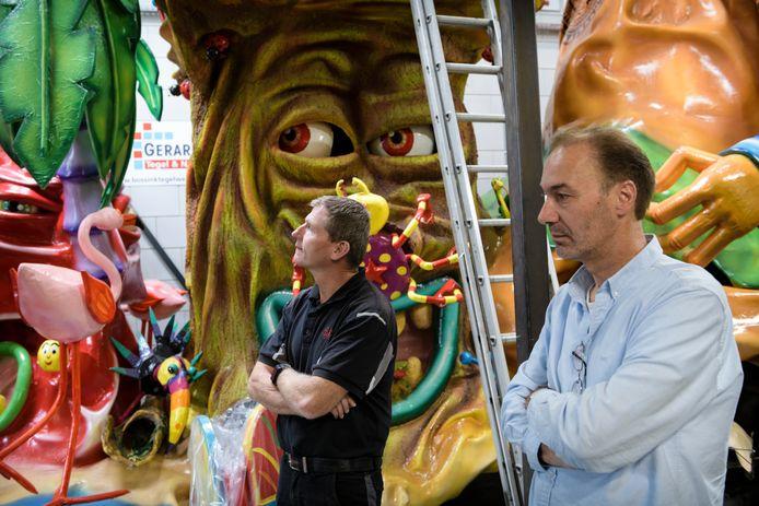 Marcel Collet (rechts) en Erwin Ikink van de Vennemuskes staan met de armen over elkaar in de carnavalsloods.