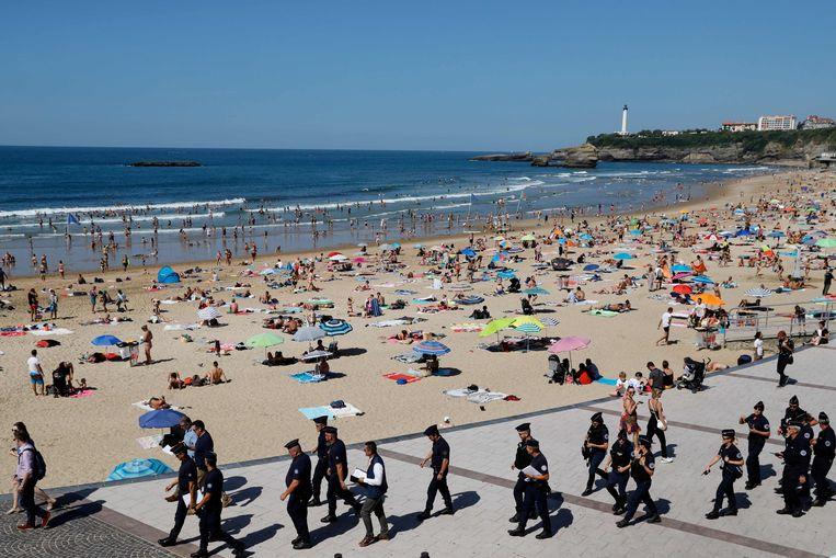 Franse ME'ers patrouilleren langs La Grande Plage, het beroemde strand van Biarritz. Hier, aan de Golf van Biskaje in Frans Baskenland, begint vandaag de top van de G7, waarop regeringsleiders van de zeven grootste industrielanden ter wereld plus de Europese Unie bij elkaar komen. Beeld AFP
