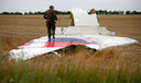 Een pro-Russische separatist loopt op de wrakstukken van MH17 op de crashsite in Oekraïne.