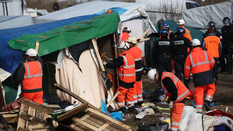 Slopers en agenten ontruimen het vluchtelingenkamp in Calais dat de bijnaam 'jungle' kreeg. Beeld getty