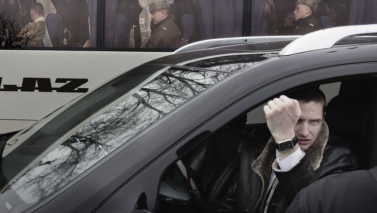 Een welgestelde inwoner van Kiev in een dure auto heeft het niet zo op fotografen. Achter hem een bus met militairen. Beeld Daniel Rosenthal