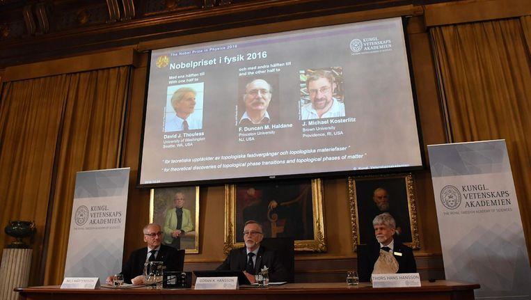 Het Nobelcomité voor een scherm met de drie winnaars erop Beeld afp