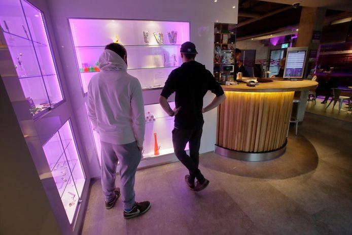 Twee bezoekers bekijken een etalage met waterpijpen en andere rookwaar in Xpresso.