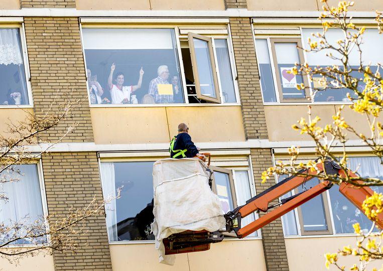 Een familielid zwaait vanuit een hoogwerker naar een geliefde in een zorgcentrum in Rijswijk. Ouderen die in een verzorgingshuis zitten mogen tijdelijk geen bezoek ontvangen door de coronacrisis.  Beeld ANP