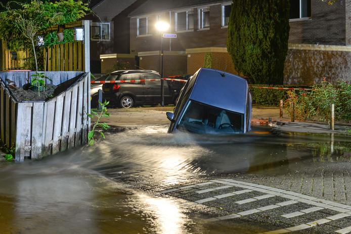 De bestuurder van deze auto dook een zinkgat in, in een woonwijk in Apeldoorn. Hij moest er uit zien te klauteren via de achterportieren.
