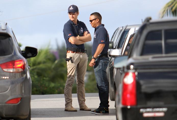 Medewerkers van de politie in 2013 voor het huis van voormalig premier van Curaçao Gerrit Schotte. Hij wordt verdacht van het witwassen van geld en valsheid in geschrifte. De vier verdachten in de rechtszaak in Zwolle eisen dat de ex-premier wordt gehoord.