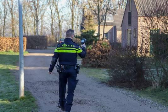 Een politieman loopt met een warmtecamera langs vakantiewoningen op recreatiepark De Groene Heuvels in Ewijk, tijdens een grootscheepse controle van politie, gemeente Beuningen en de Belastingdienst.
