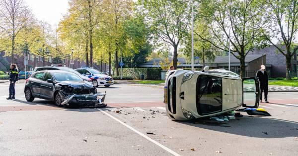 Auto op zn kant na botsing in Tilburg: bestuurders nagekeken door ambulancemedewerkers.