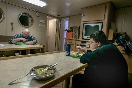 Gert Lokker en Henk Bakker (r) aan de maaltijd. De vissersmannen praten nauwelijks aan boord. ,,Ze hebben weinig woorden nodig.''