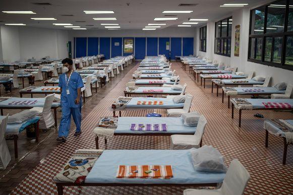 Een ziekenhuismedewerker in New Delhi loopt langs de rijen bedden voor Covid-19-patiënten in een noodhospitaal.
