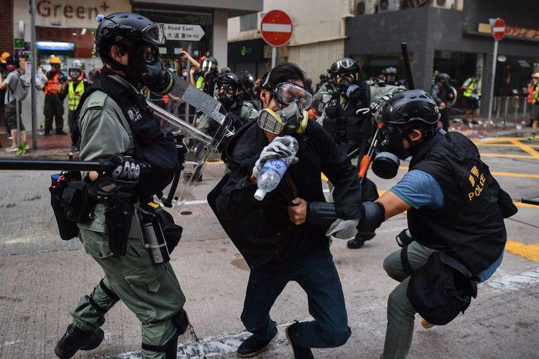 De Chinese politie pakt een demonstrant op in Hongkong. Beeld AFP