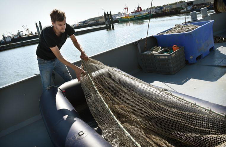 Kokkelvisser Arjen de Bock maakt een net klaar. Beeld Marcel van den Bergh