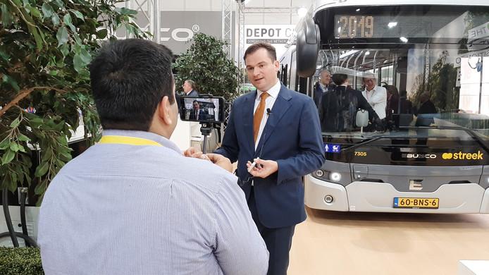 Peter Bijvelds van Ebusco voor een bus van zijn bedrijf op de beurs Busworld in Brussel.