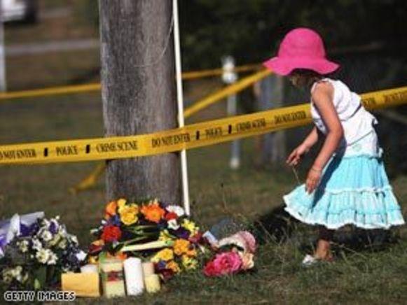 Een meisje legt bloemen neer op de plaats waar de toeriste werd vermoord.