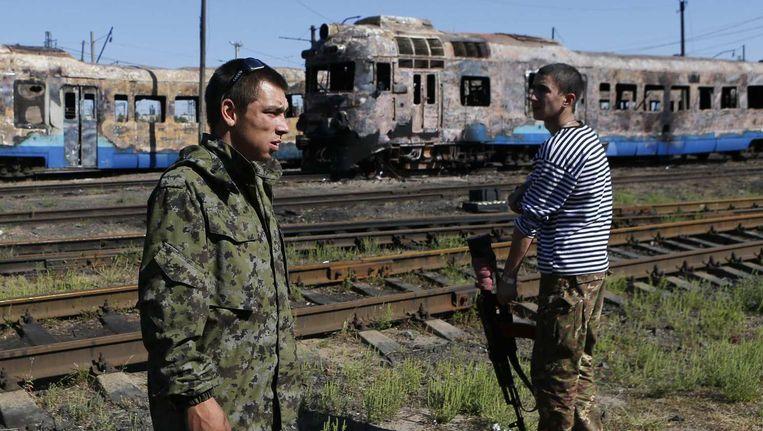 Pro-Russische separatisten bij een verwoeste trein bij het Oekraïense stadje Ilovaysk. Beeld reuters