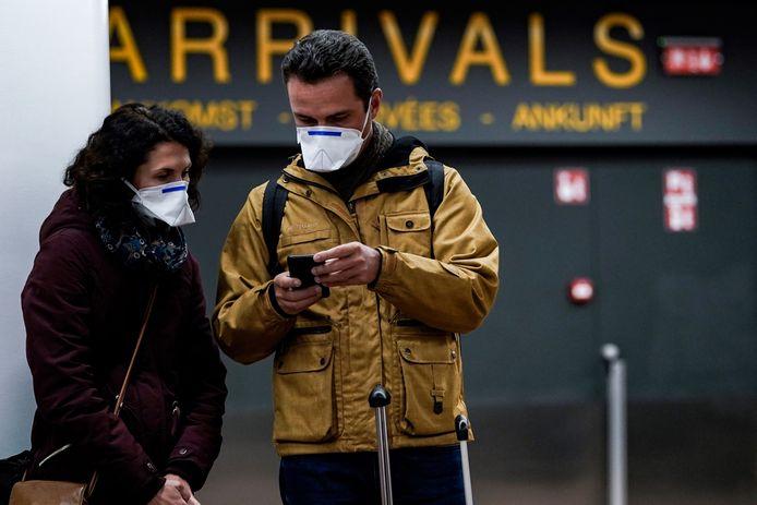 Passagiers met mondmaskers in de aankomsthal van Brussels Airport in Zaventem, archiefbeeld ter illustratie.