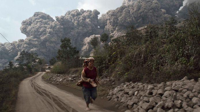 Een man rent voor een uitbarsting van vulkaan Sinabing op Sumatra.