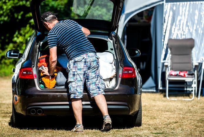 Een vakantieganger pakt zijn auto in op de camping.