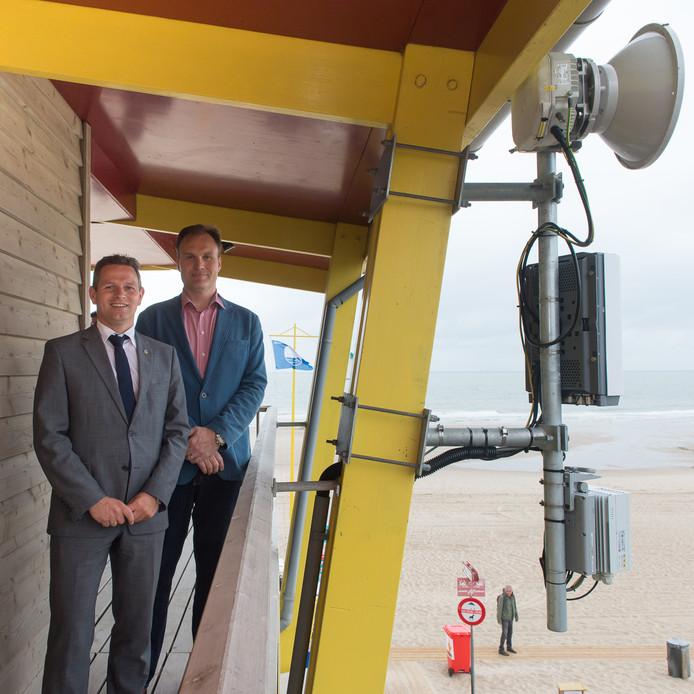 Vodafone-topman Eben Albertyn (rechts) en provinciebestuurder Jo-Annes de Bat bij de schotelantenne en small-cell die gemonteerd zijn aan de strandpost in Domburg. Deze apparatuur zorgt voor mobiel bereik op de stranden van Walcheren en Noord-Beveland.
