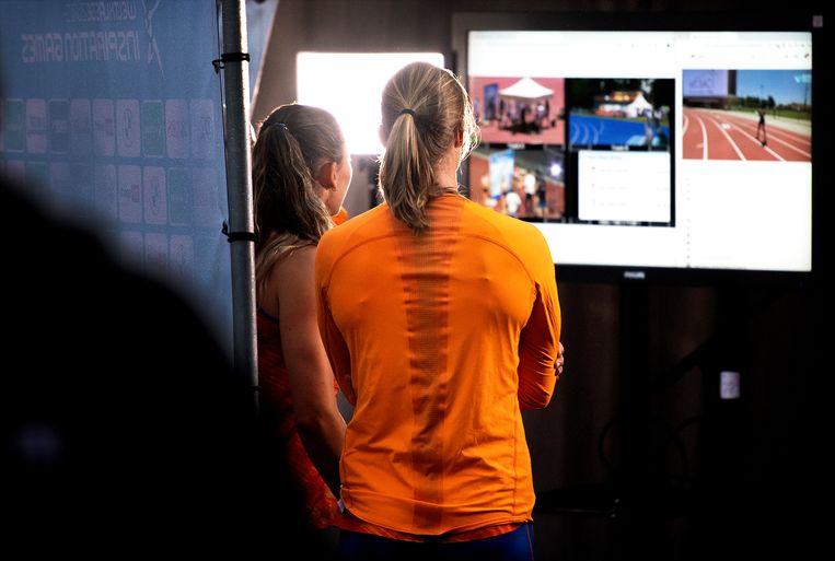 Dafne Schippers en Nadine Visser ( links ) kijken na afloop van hun 3 x 100 meter estafette op Papendal naar het scherm waar beelden uit de andere wedstrijdsteden te zien zijn. Beeld Klaas Jan van der Weij