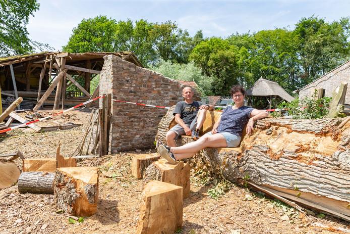 Taco en Aafke Jongman kunnen weer even ademhalen en ploffen neer op een uitgezaagde boomstam. De stam is een 'erfenis' van de grote windhoos. Op de achtergrond is de schade aan de scheur nog duidelijk zichtbaar.