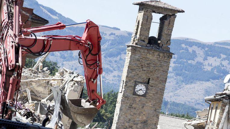 Met behulp van een graafmachine is de brandweer in Amatrice aan het puinruimen. Beeld EPA