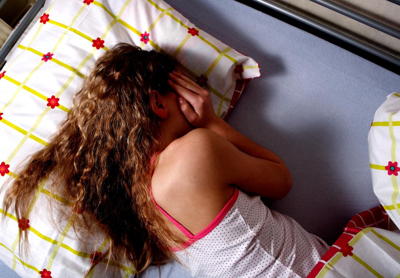 Foto ter illustratie - Een meisje ligt op bed.