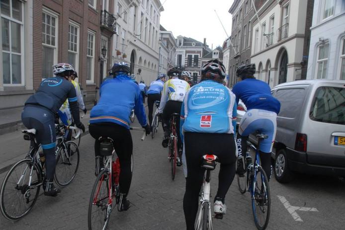 De renners rijden kort na hun vertrek door de Peperstraat.