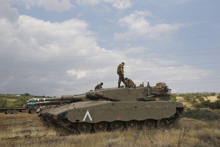 Een Israëlische soldaat staat bovenop een Markava IV tank aan de grens met Syrië. Beeld null