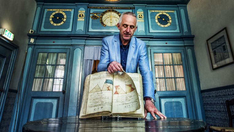 Directeur Adrie Warmenhoven met Eise Eisinga¿s aantekenboek uit circa 1760. `Een leergierige 17-jarige.` Beeld raymond rutting