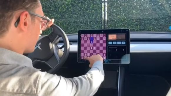 Fabiano Caruana schaakt tegen een Tesla.