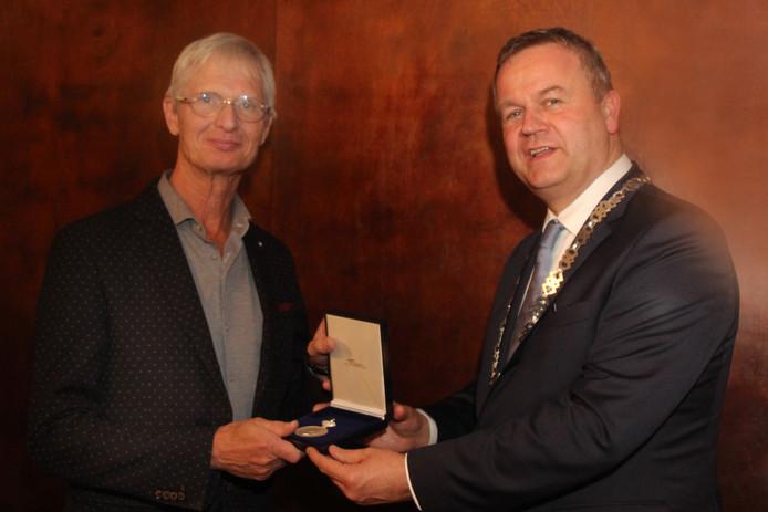 Voorzitter Fred van Brederode (links) neemt de erepenning in ontvangst van burgemeester Van Stappershoef.