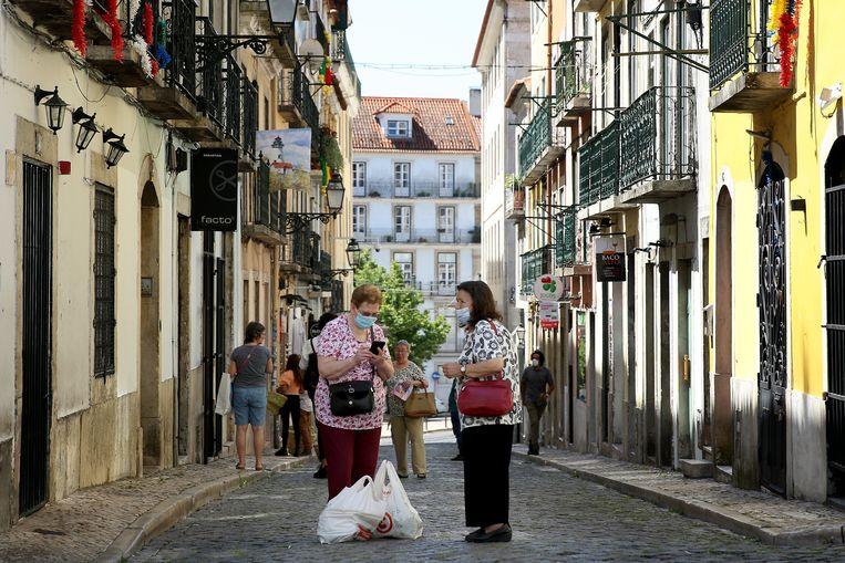 Mensen met mondmaskertjes op op straat in Lissabon.